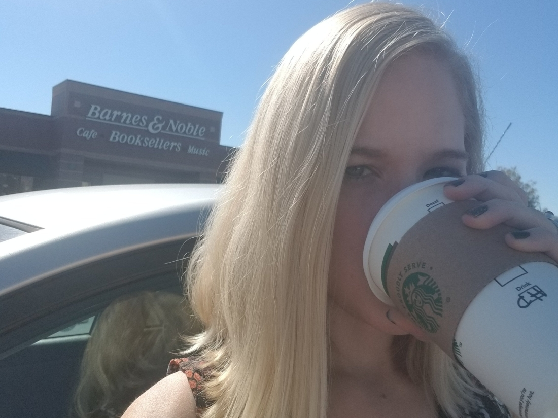 Annoyed blonde drinking a coffee outside a bookstore